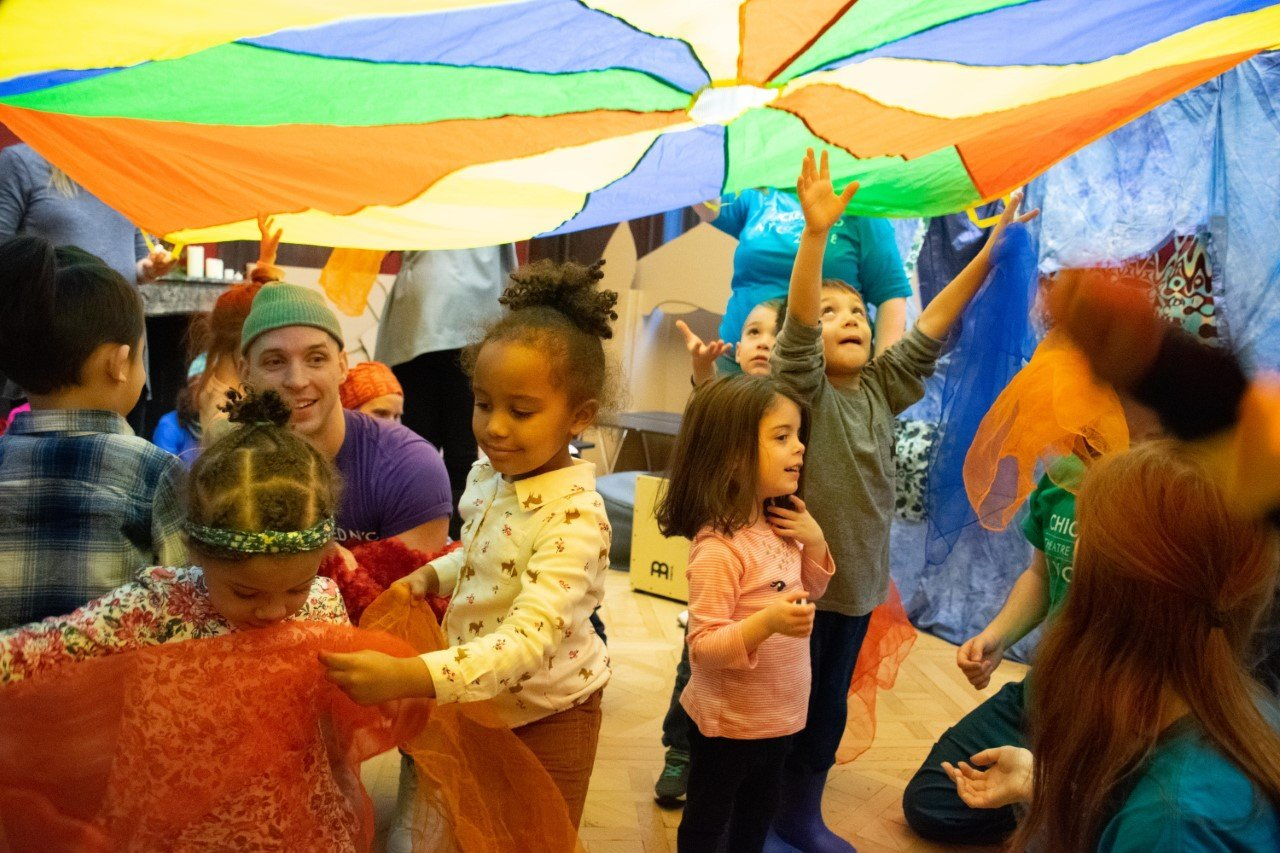 kids playing under rainbow parachute